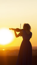 Silhouette Of A Female Figure In Long Dress Playing The Violin At Sunset, Woman Relaxing In Music, Performance On Nature, Concept Art And Hobby