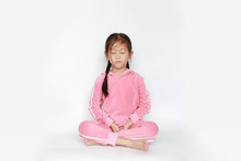 Portrait Of Beautiful Little Asian Child Girl In Pink Tracksuit Or Sport Cloth Sit In Meditation And Peace Stance Over White Background. Peaceful Concept.