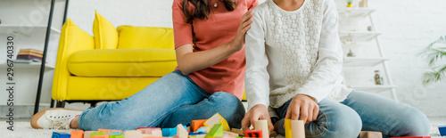 panoramic shot of babysitter and kid near toy blocks in living room Wallpaper Mural