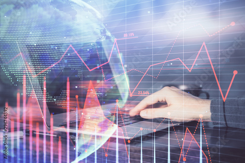 Photo Stands Amsterdam Double exposure of man's hands writing notes with laptop of stock market with forex graph background. Top View. Concept of research and trading.