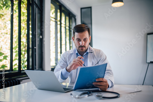 Portrait of a doctor doctor reviewing document in medical office.