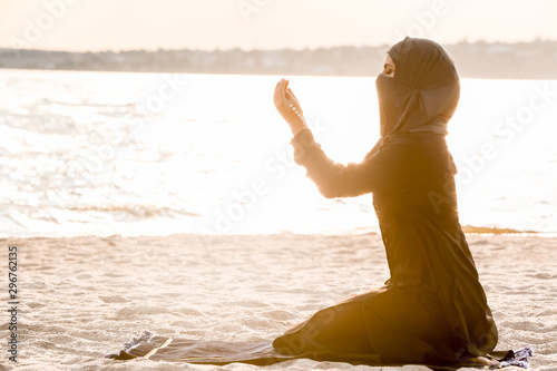 Beautiful Muslim woman praying near river Wallpaper Mural
