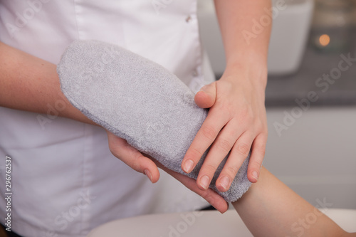Female hand in beauty spa salon with paraffin wax in glove Fototapet