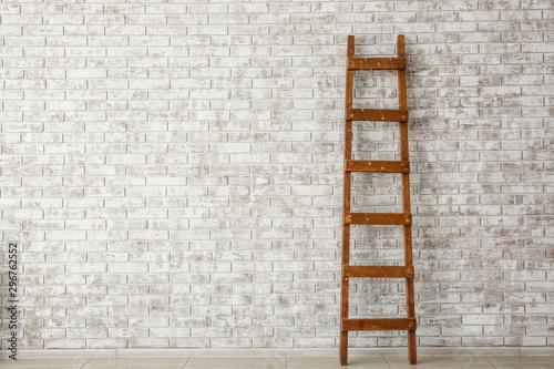 Fotografie, Obraz Wooden ladder near brick wall