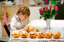 Little Kid Boy Making Jack-o-lantern With Drawing Scary Faces On Mandarine, Tangerine Or Clementine. Happy Child Making Preparation For Halloween Party At Home, Indoors