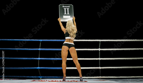 Photo  back boxing ring girl carrying sign that displays number of upcoming round