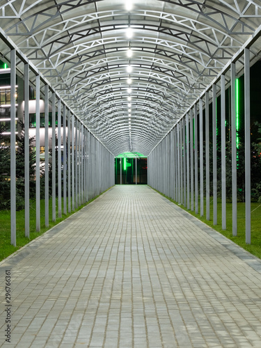 Fényképezés  Futuristic pedestrian overpass tunnel with bright lighting, receding into the distance at night