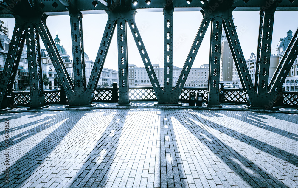The road bridge with all steel beams in the sunlight has clear steel beam shadow on the road surface