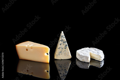 Fotomural  Various types of cheeses: camembert, brie, blue cheese, maasdam on black background with reflection