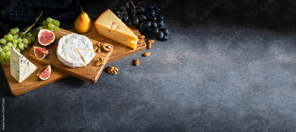 Fototapety, obrazy: Cheese plate served with camembert, brie, blue cheese, maasdam, grapes, pear, figs and nuts on a wooden board on gray background. Side view, copy space. Banner