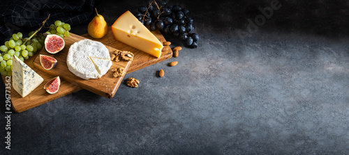 Fotografía  Cheese plate served with camembert, brie, blue cheese, maasdam, grapes, pear, figs and nuts on a wooden board on gray background