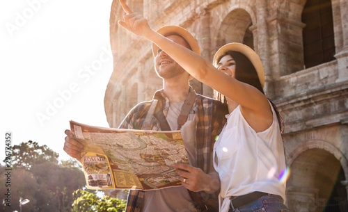 Pinturas sobre lienzo  Lovely couple of tourist at Colosseum reading city map guide