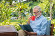Senior elderly man reading book drinking mug of coffee in garden