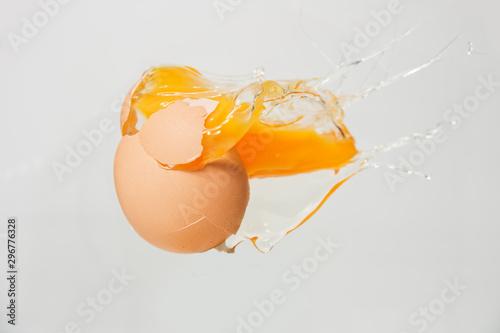 Fotografía  cracked egg with yolk on white background