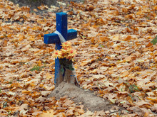 Old Wooden Cross On A Grave In A Cemetery In Autumn