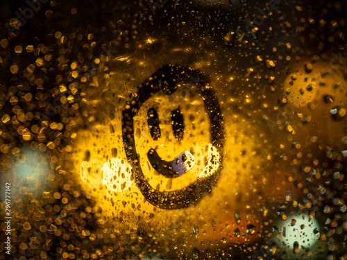 Photo Smiley face painting on a glass of a steamy window