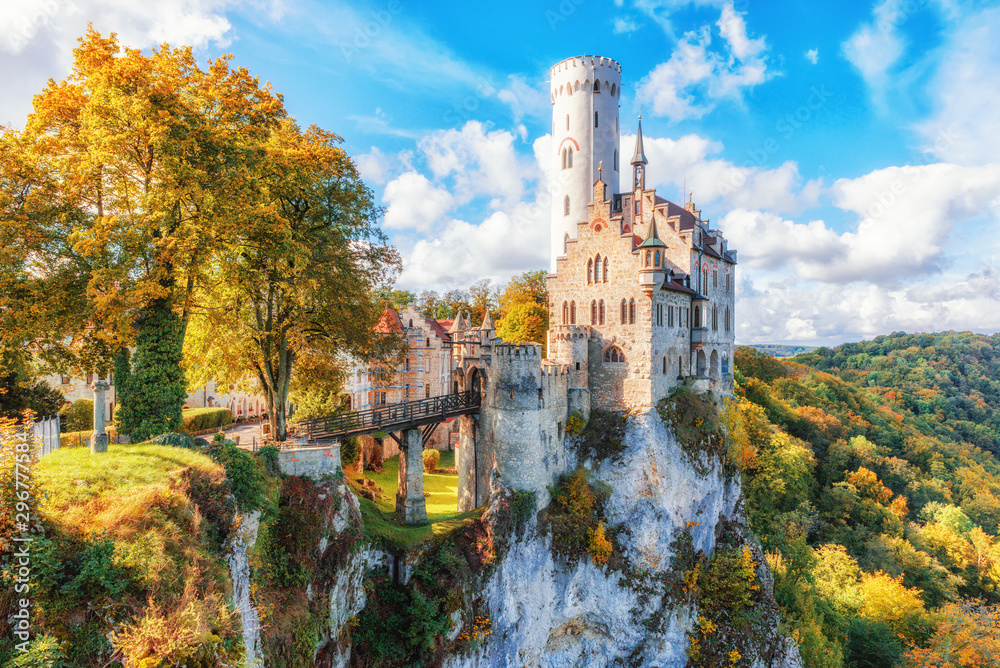 Fototapety, obrazy: Germany, Lichtenstein Castle in Baden-Wurttemberg land in Swabian Alps. Seasonal view of  Lichtenstein Castle on a cliff circled by trees with yellow foliage. European famous landmark.