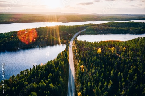 Leinwand Poster Aerial view of bridge across blue lakes with sun light in colorful autumn forest in Finland
