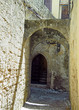narrow alleyway in rhodes old town with arches between old stone walls and an open doorway with stairs inside