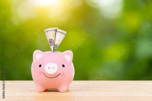 Pink piggy bank on wooden desk with dollar banknote inserted, on green tree back Fototapet