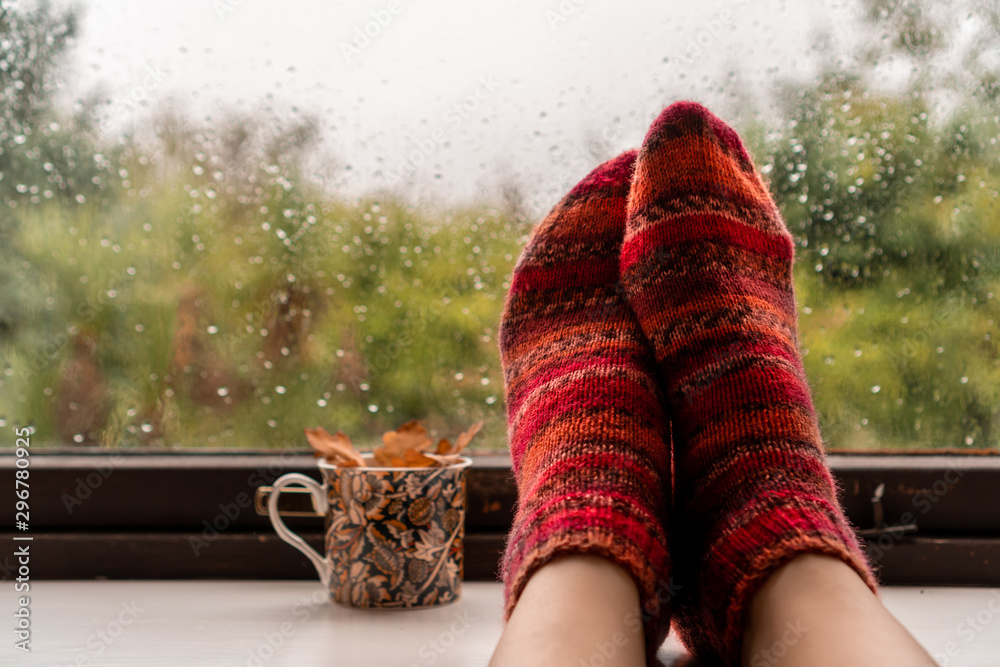Fototapety, obrazy: Woman feet in warm wool socks next to colourful mug with fall leaves against a rainy widow background. Autumn rain and cold weather concept.