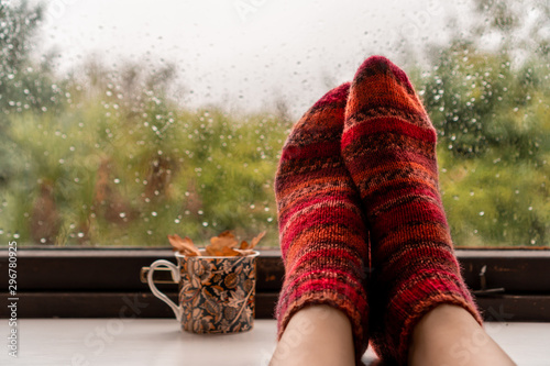 Foto Woman feet in warm wool socks next to colourful mug with fall leaves against a rainy widow background
