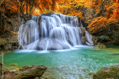 Beautiful and colorful waterfall in deep forest during idyllic autumn