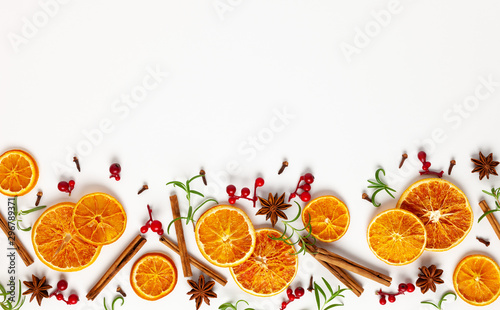 Christmas composition with dried oranges, cinnamon sticks and herbs on white background. Natural food ingredient for cooking or Christmas decor for home. Flat lay.