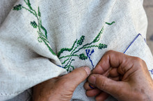 Hands Of An Elderly Woman Embroidering A Cross-stitch Floral Pattern On Linen Fabric. Embroidery, Handwork, Needlecraft Concept. Closeup