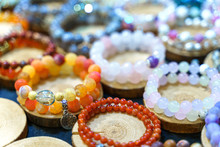 Variety Of Handmade Beautiful Stone Bracelets On Wooden Stand