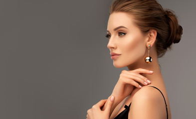 Beautiful girl . Fashionable and stylish woman in trendy jewelry big earrings . Fashion look , beauty and style. Natural makeup & easy styling