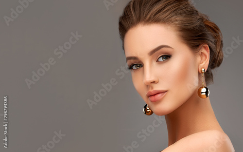 Fototapeta Beautiful girl . Fashionable and stylish woman in trendy jewelry big earrings .  Fashion look  , beauty and style. Natural makeup & easy styling obraz