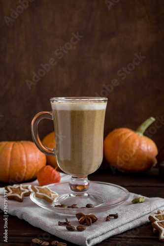 One Pumpkin spice latte in a tall glass on a wooden background. Autumn mood. Cinnamon, pumpkin, cloves, spices and cookies. Side view, close-up, copy space.