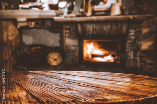 Obraz Wooden top with cosy warm home interior with fireplace background. - fototapety do salonu