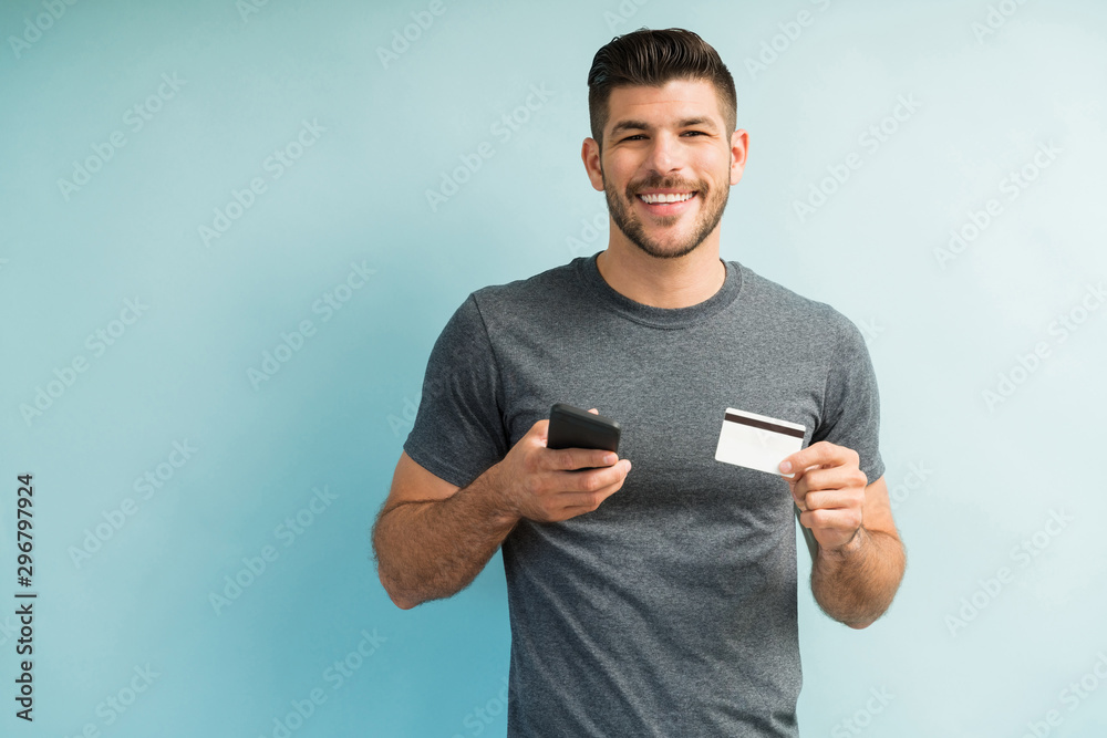 Fototapeta Smiling Attractive Man Making Online Payment