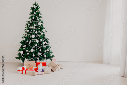 Foto op Canvas Bomen Green Christmas tree with gifts of toys for the new year holiday decor winter