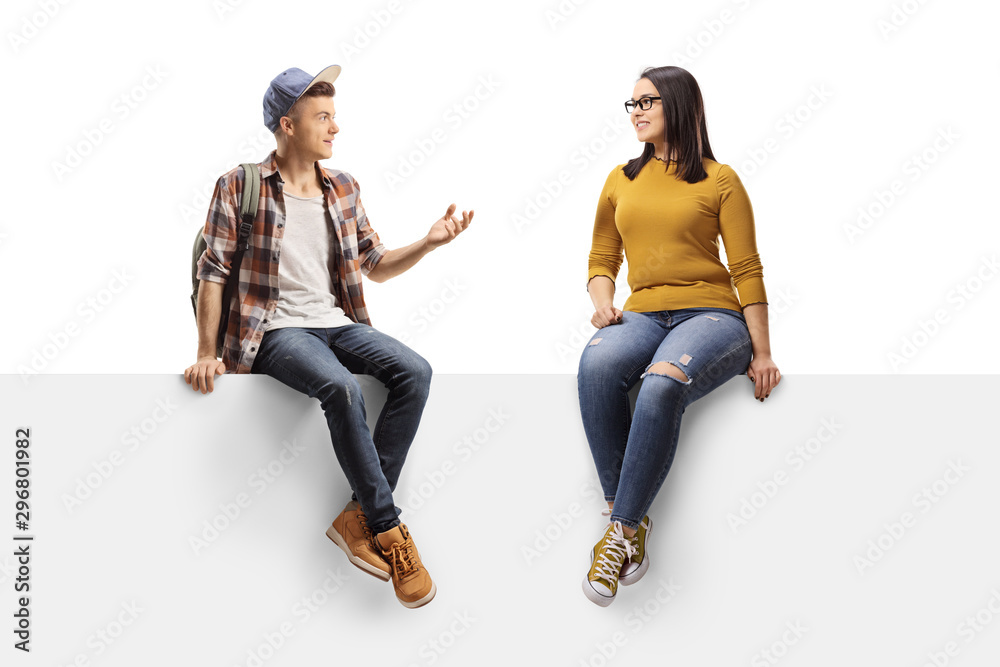 Fototapety, obrazy: Male student sitting on a panel and talking to a female friend