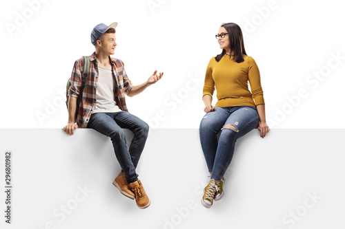 Fotografia  Male student sitting on a panel and talking to a female friend