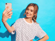 Portrait of cheerful young woman taking photo selfie. Beautiful girl holding smartphone camera. Smiling model posing near blue wall in studio