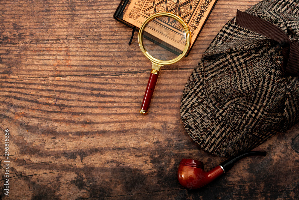 Fototapeta Literary fiction, investigate crime and mystery story conceptual idea with sherlock holmes detective hat, smoking pipe, retro magnifying glass and old book isolated on wood table top with copy space