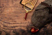 Literary Fiction, Investigate Crime And Mystery Story Conceptual Idea With Sherlock Holmes Detective Hat, Smoking Pipe, Retro Magnifying Glass And Old Book Isolated On Wood Table Top With Copy Space