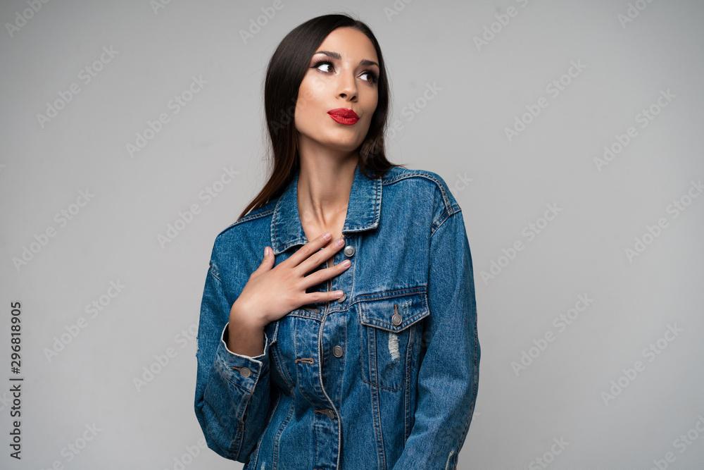 Fototapeta Beautiful caucasian girl in a denim jacket posing in the studio on a white background.