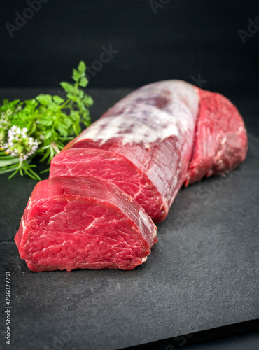 Photo Dry aged beef fillet steak natural with a bouquet garni as closeup on black back