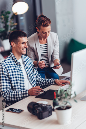Graphic designer working on computer and talking with colleague