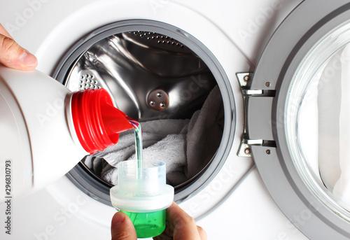 Fototapeta liquid detergent bottle pour washing machine hand obraz