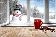 Small Smiling Snowman In A Hat And Scarf With White Snowy Winter Background With Space For Your Products And Decoration. Blurred Landscape Of Trees Covered With Snow Outside The Window Christmas Time.