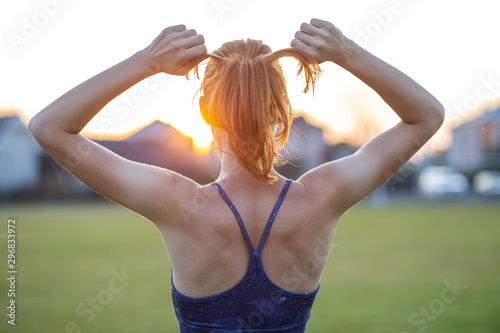 Closeup of yong sportive woman with red hair standing outdoors with raised arms enjoying sunrise before training.