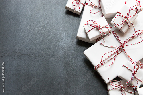 Fototapeta Flat lay composition with Christmas gifts boxes with red ribbon on black background, copy space. Winter holiday pattern. Top view obraz