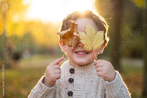 Szczęśliwa małego dziecka chłopiec śmia się i bawić się w jesieni
