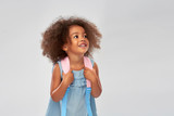 childhood, school and education concept - happy little african american girl with backpack over grey background